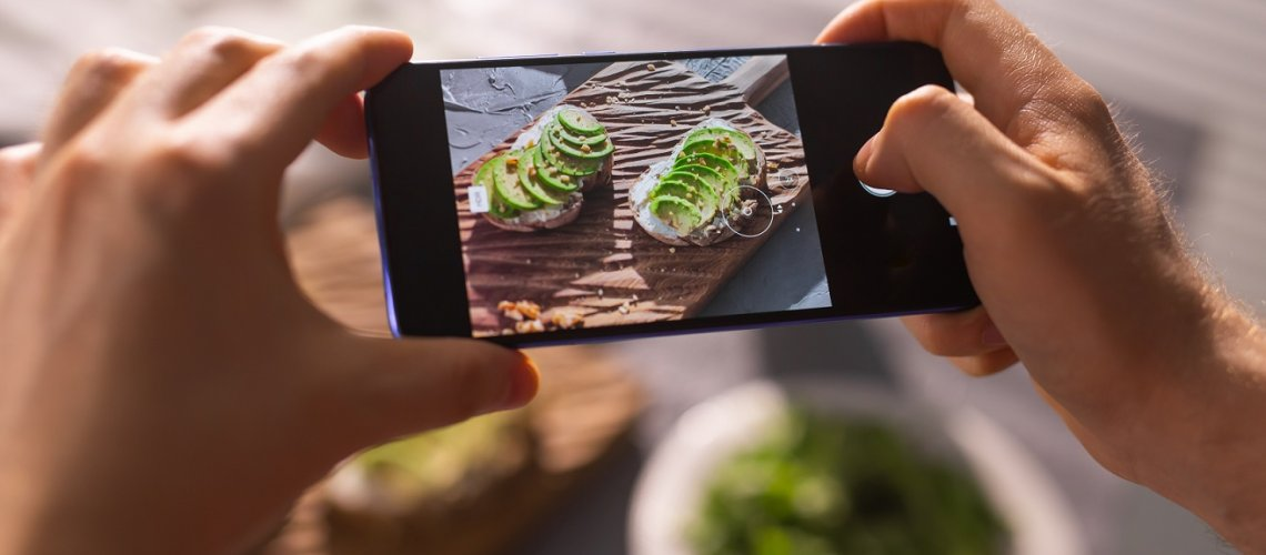 Hands take pictures on smartphone of two beautiful healthy sour cream and avocado sandwiches lying on board on the table. Social media and food